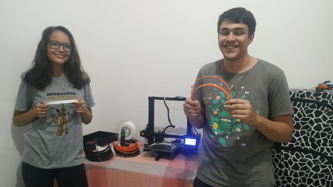Os estudantes Múria Viana e Joiro Gomes Neto são voluntários na campanha e estão ajudando na produção dos suporte para protetores faciais.